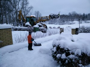 Ett litet barn tittar på en stor traktor som sköter snöröjningen